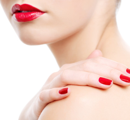 Close-up photo of a beautiful red female lips. Hand with beauty manicure on a shoulder
